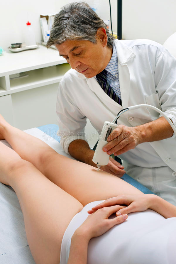 Кавказская женщина получая обработку лазера на ноге от мужчины стоковая фотография rf