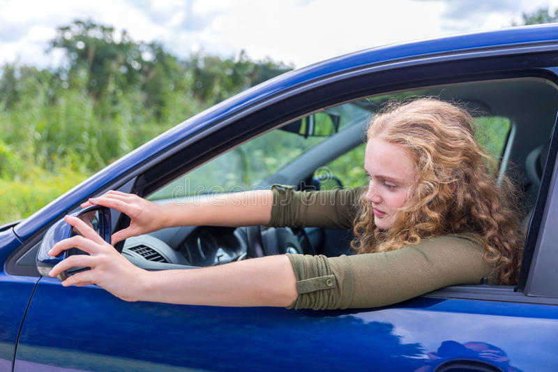Кавказская женщина регулируя бортовое зеркало автомобиля стоковое изображение rf