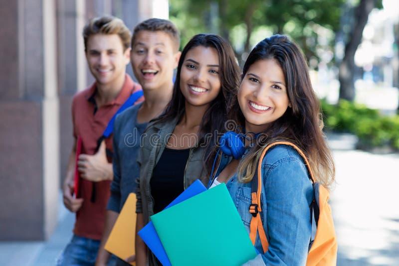 Кавказская молодая взрослая женщина с группой в составе студенты в линии стоковые изображения rf