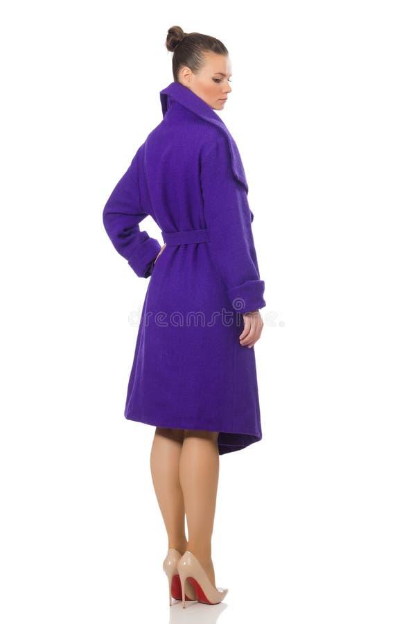 Кавказская модель в фиолетовом пальто изолированном на белизне стоковая фотография rf