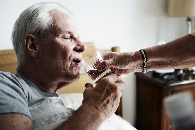 Кавказская питьевая вода старшего человека в его кровати стоковые фото