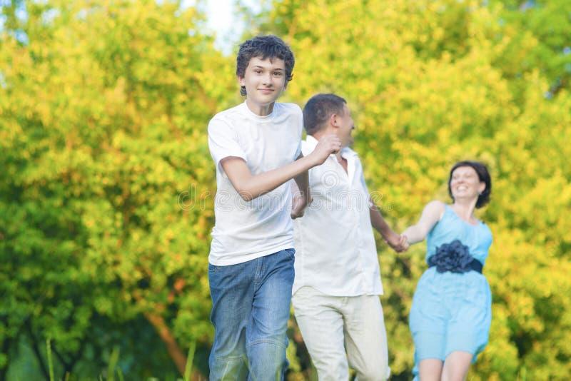Кавказская семья из трех человек имея потеху совместно и бежать в лесе лета с соединенными руками Outdoors стоковые фотографии rf