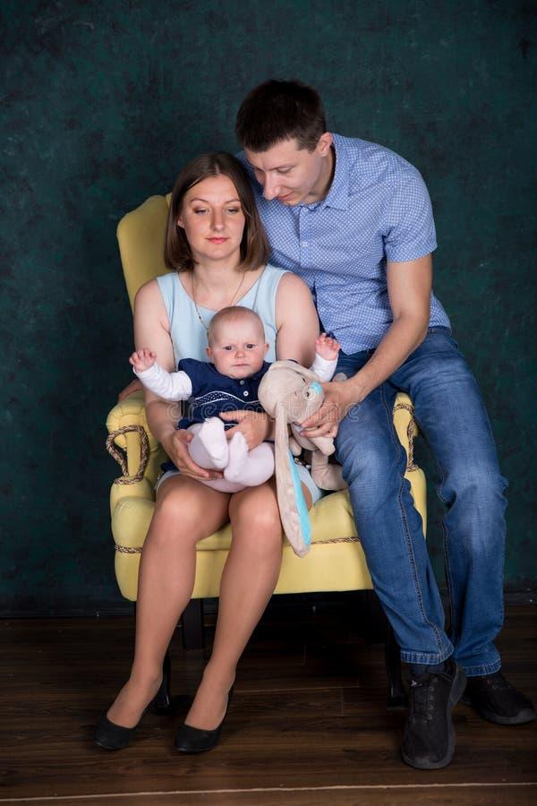 Кавказская семья представляя на большом кресле в студии стоковые изображения rf