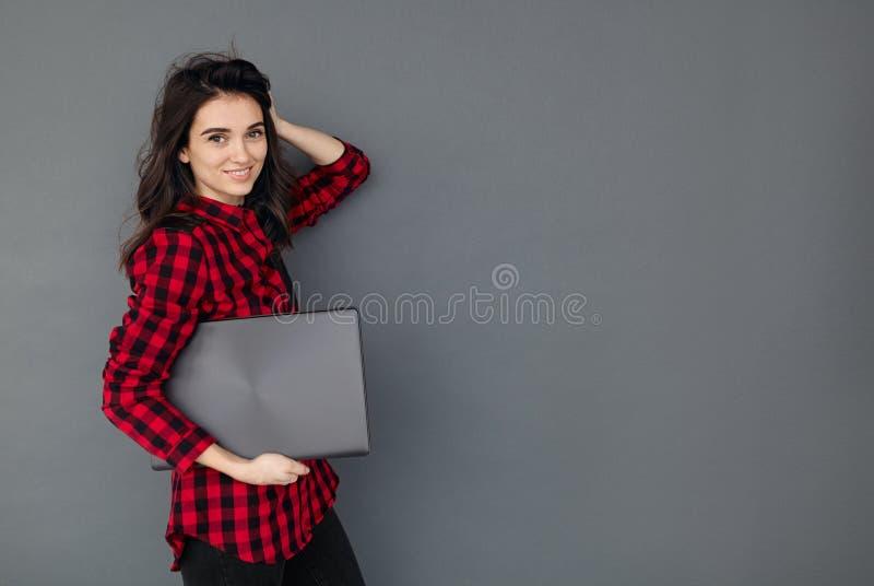 Кавказская усмехаясь девушка студента держа компьтер-книжку над серой предпосылкой стоковое фото rf