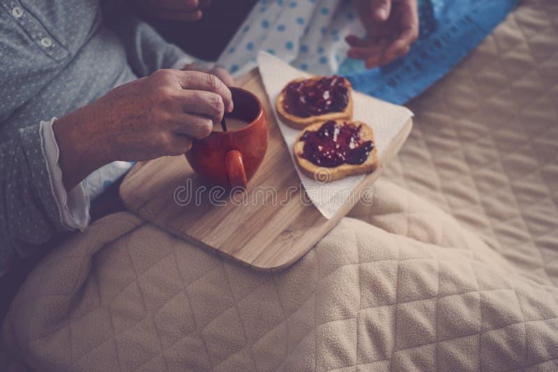 Кавказские достигшие возраста пары делая завтрак дома в кровати славная естественная сцена дома для концепции жизни togheterness  стоковые изображения rf