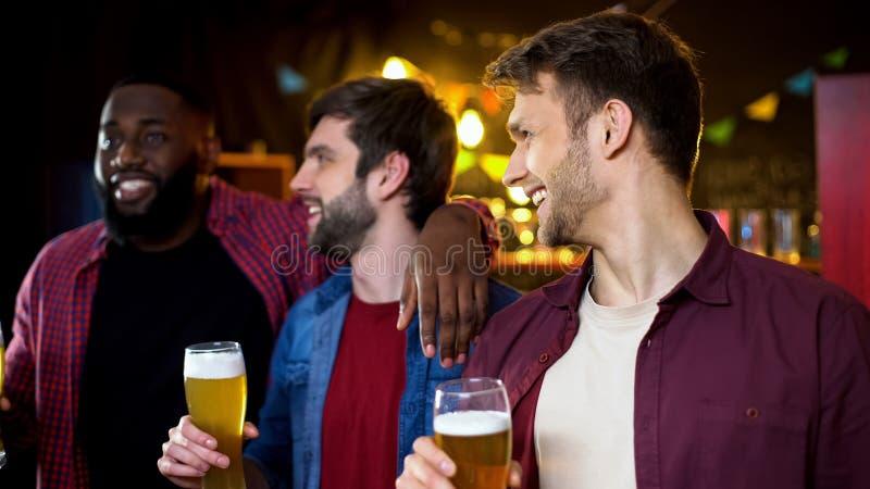 Кавказские друзья смотря их Афро-американского друга, выпивая пива в баре стоковое изображение