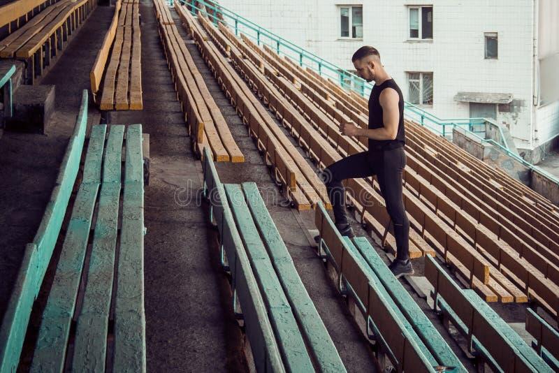 Кавказские поезда человека в беге на лестницах Бегун легкой атлетики в тренировке спорта равномерной на открытом воздухе t шаг стоковое изображение rf