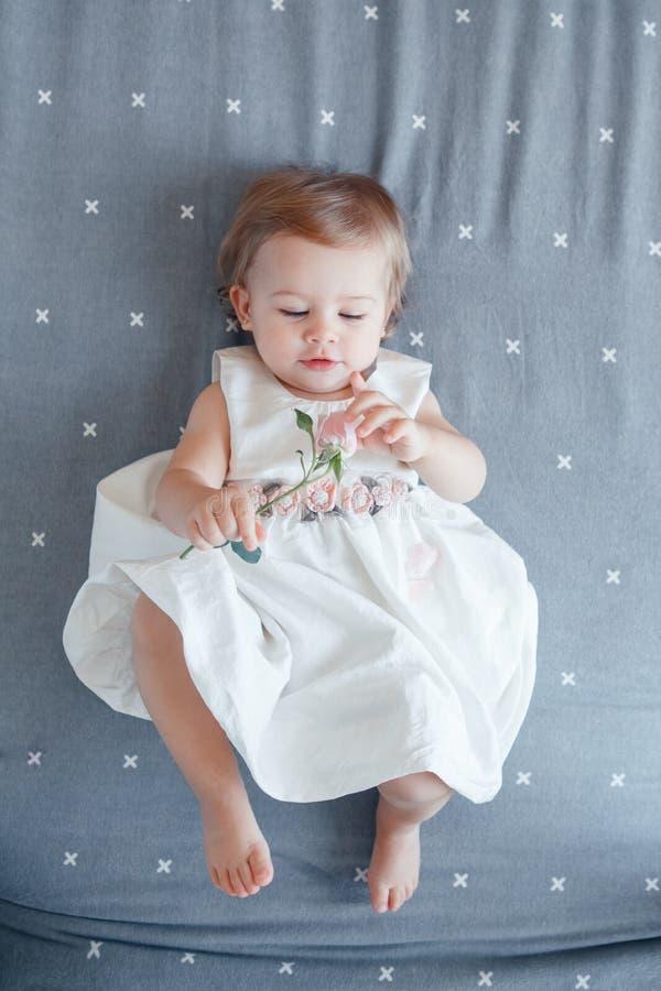 Кавказский белокурый ребёнок одно годовалый в белом платье лежа на серой простыне в спальне, взгляде от верхней части стоковое фото
