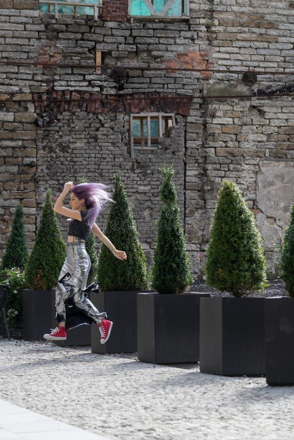 Кавказский белый женский камень модели и кирпича Красивая девушка при длинные фиолетовые волосы отдыхая в городе, современная кон стоковое изображение