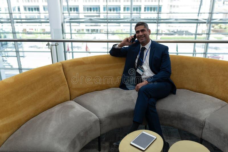 Кавказский бизнесмен говоря на мобильном телефоне в лобби офиса стоковое изображение