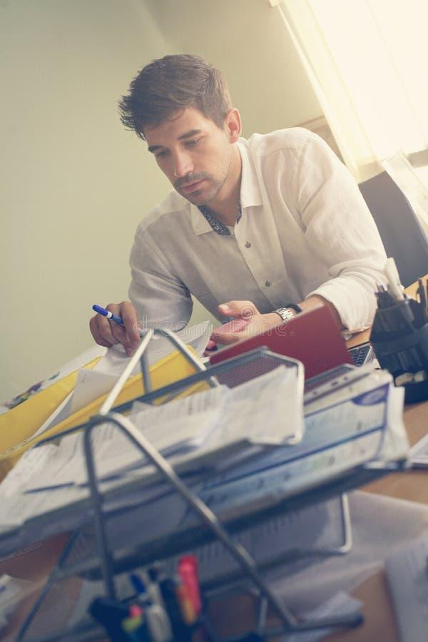 Кавказский бизнесмен работая на его столе стоковые изображения rf