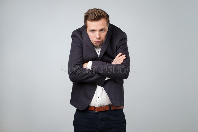 Кавказский молодой человек в слишком большом костюме Он обиден и посмотрен усилен стоковое фото rf