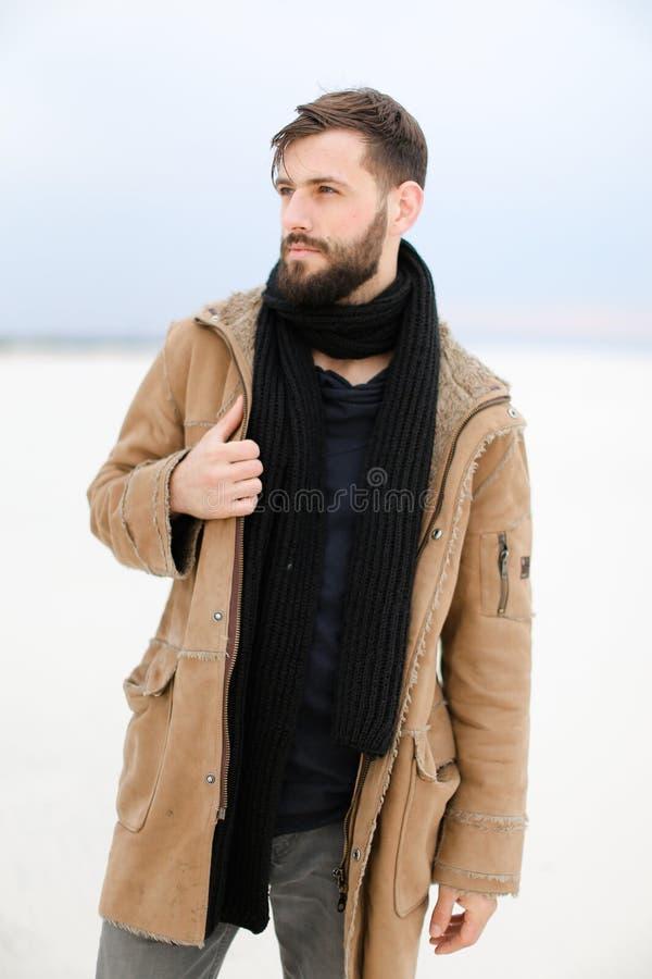Кавказский мужск человек при пальто и шарф бороды нося стоя в белой предпосылке снега стоковые изображения rf