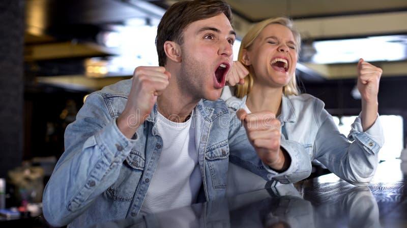 Кавказский мужчина и женское кричащее, радующся победа команды, пары вентиляторов стоковые изображения rf