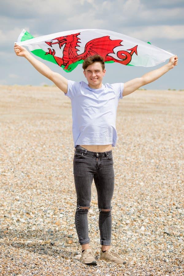 Кавказский мужчина на пляже держа флаг валийца стоковое изображение