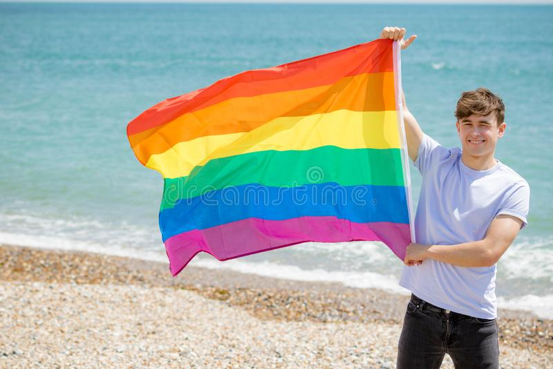 Кавказский мужчина на пляже держа флаг гордости стоковое фото