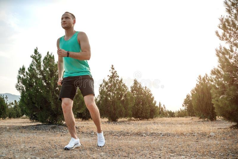 Кавказский парень в голубой футболке и черных шортах, бежать над пересеченной местностью тренировка во время захода солнца стоковая фотография
