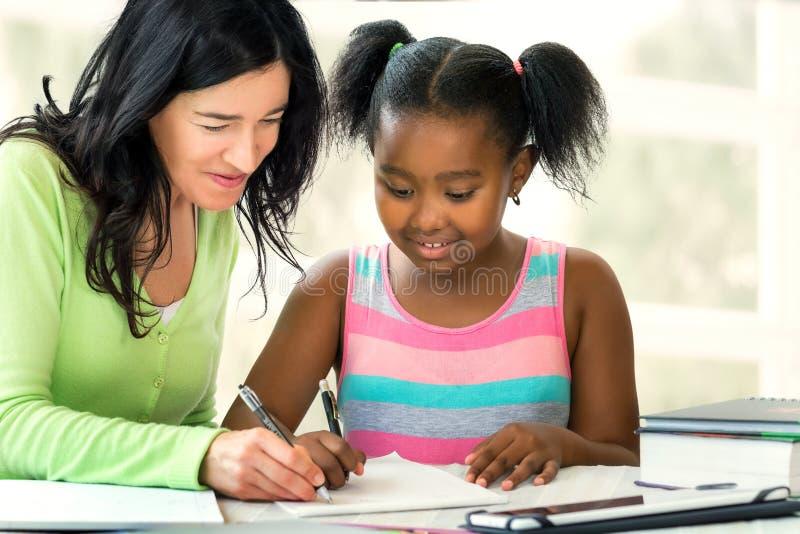 Кавказский учитель помогая маленькому африканскому студенту на столе с sc стоковые изображения