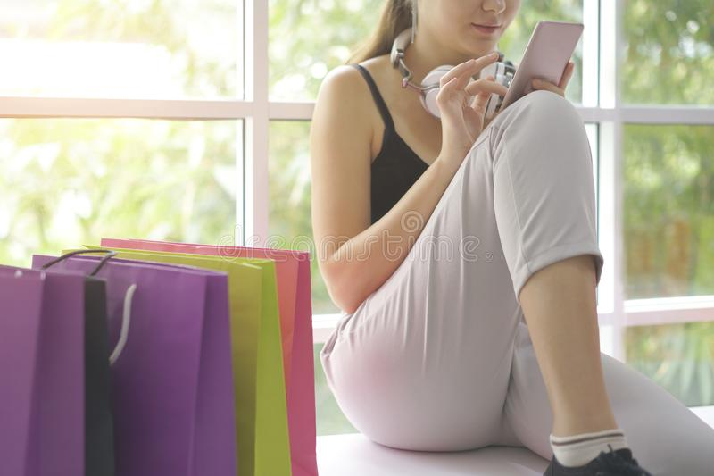 Кавказский ходить по магазинам девушки онлайн с магазином интернета смартфона, вебсайтом электронной коммерции на черни стоковое изображение