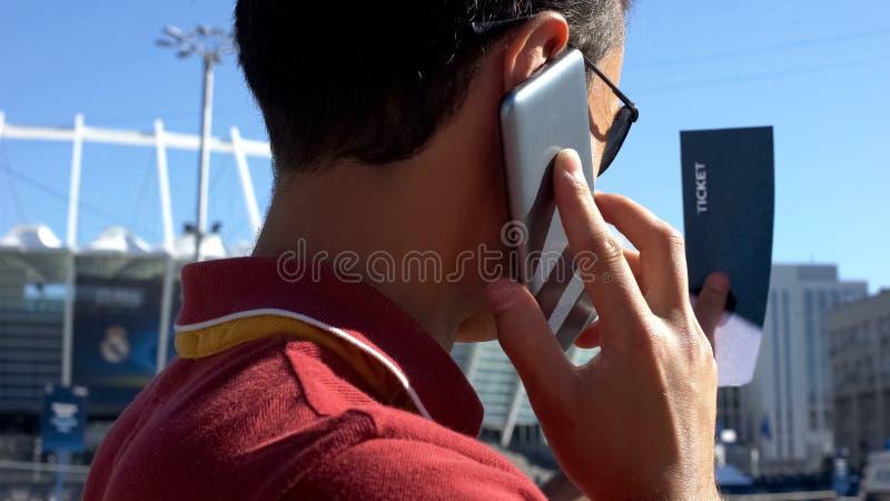 Кавказский человек говоря на мобильном телефоне, держа билет футбола в руке, конец-вверх стоковое фото rf