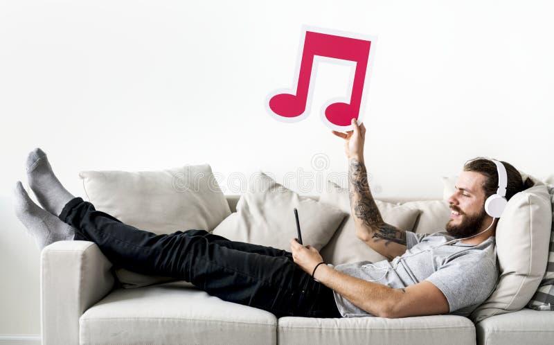 Кавказский человек наслаждаясь музыкой дома держа музыкальное примечание стоковые фотографии rf