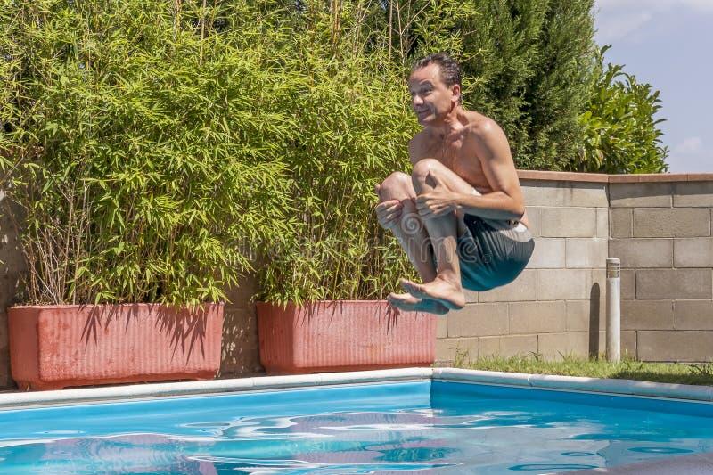 Кавказский человек принимает пикирование бомбы в бассейне стоковая фотография