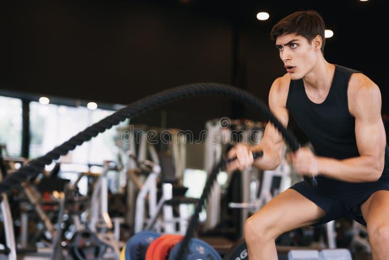 Кавказский юноша, который делает упражнения с боевым тросом силы и мотивации в тренажерном зале, фитнес стоковые фото