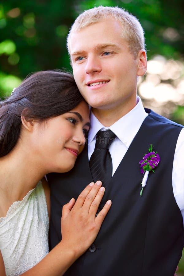 Кавказский groom держа его biracial невесту, усмехаясь Разнообразное cou стоковая фотография