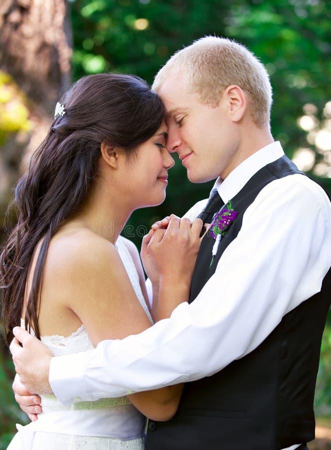 Кавказский groom держа его biracial невесту, усмехаясь Разнообразное cou стоковые фото