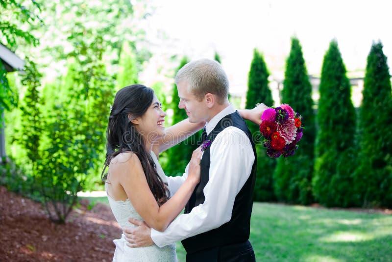 Кавказский groom держа его biracial невесту, усмехаясь Разнообразное cou стоковое фото