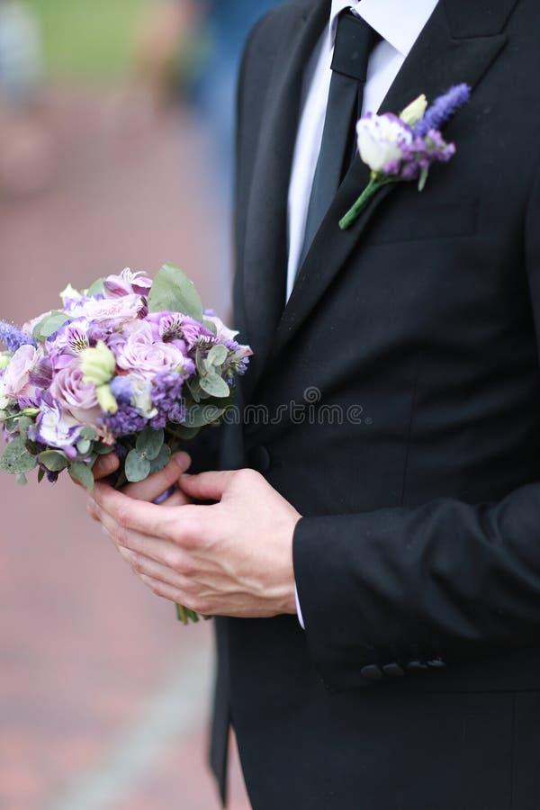 Кавказский groom нося черный костюм и связь держа букет цветков стоковые фото