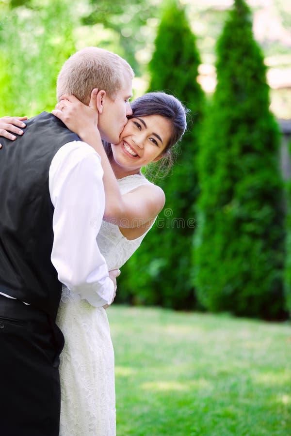 Кавказский groom любяще целуя его biracial невесту на щеке Di стоковые изображения