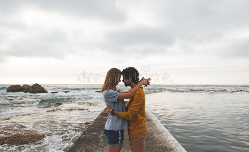 Кавказское положение пар на утесе около пляжа стоковые изображения