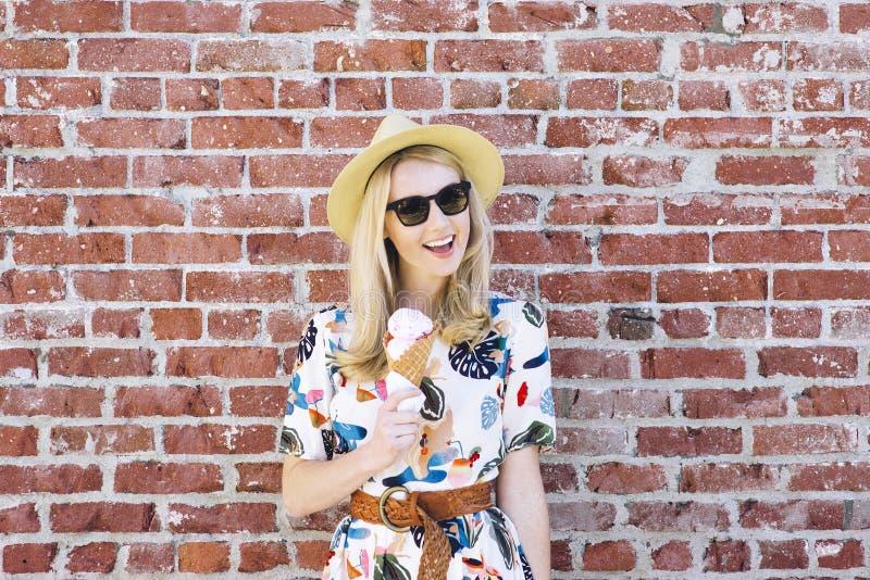 Кавказское тысячелетнее ест конус мороженого на солнечный день с тенями и усмехаться шляпы Fedora счастливым стоковое изображение rf