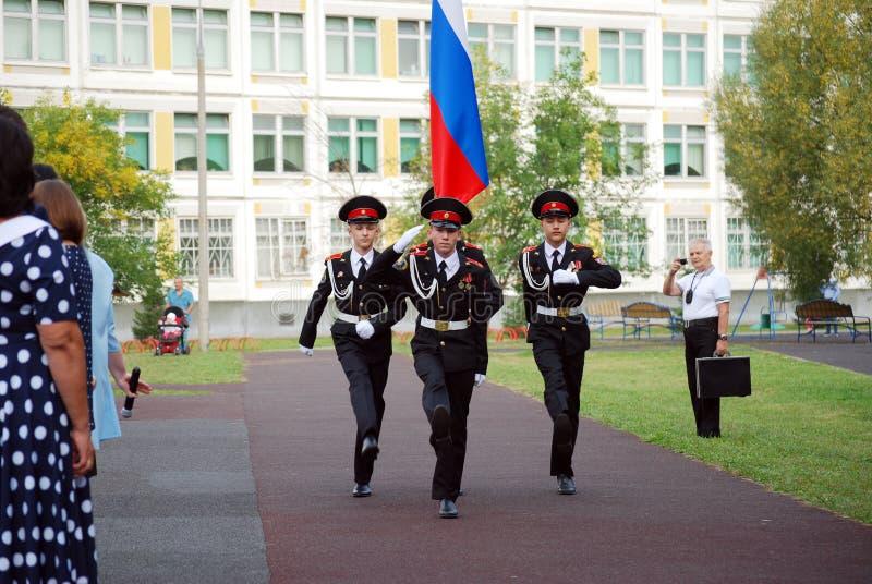 Кадеты маршируют со знаменем на правителе утра перед школой на плаце Студенты школы стоковые фотографии rf