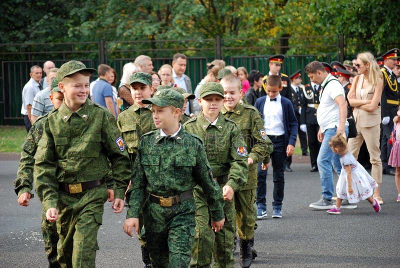 Кадеты маршируют со знаменем на правителе утра перед школой на плаце Студенты школы стоковые фото