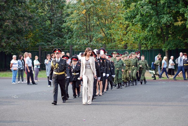 Кадеты маршируют со знаменем на правителе утра перед школой на плаце Студенты школы стоковое изображение rf
