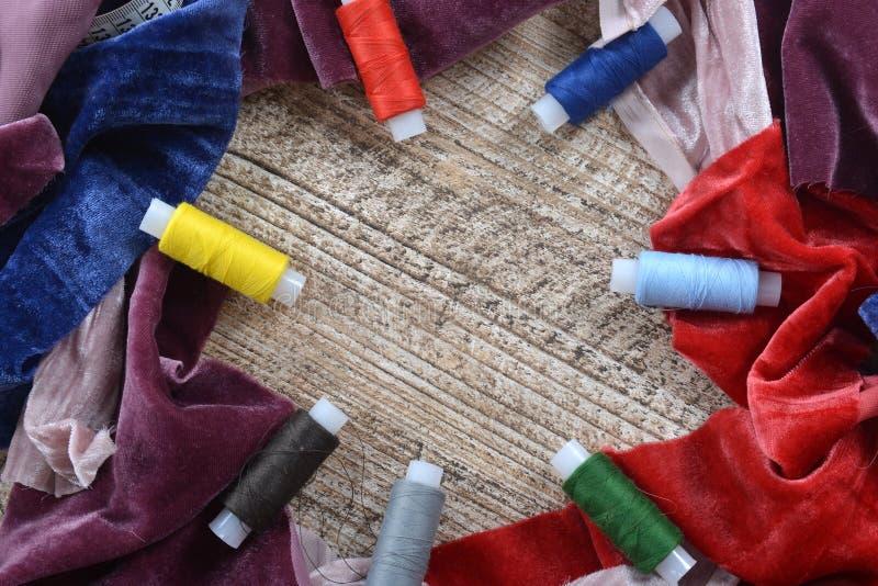 Кадр из кусков ткани с измерительным сантиметром и катушками многоцветных нитей Обрезка ручной работы стоковые изображения