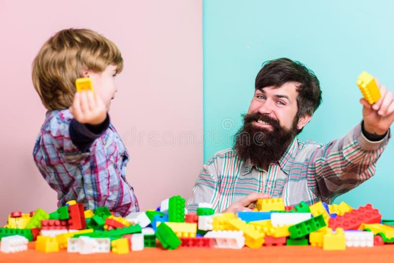 Каждые папа и сын должны сделать совместно Папа и ребенк построить пластиковые блоки Развитие ухода за детьми : Сын отца стоковые фото