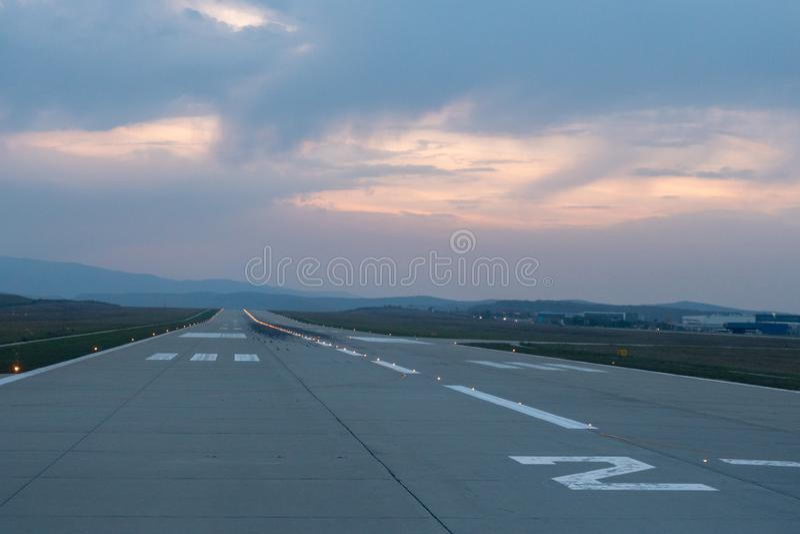 Кажется, что идет взлетно-посадочная дорожка аэропорта к горизонту захода солнца стоковые изображения rf