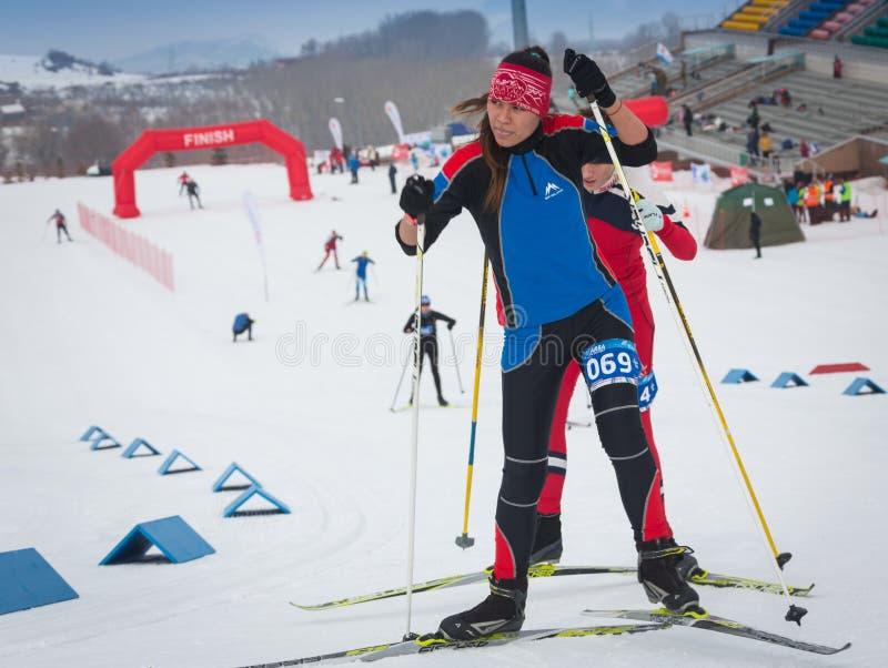 КАЗАХСТАН, АЛМА-АТА - 25-ОЕ ФЕВРАЛЯ 2018: Конкуренции беговых лыж дилетанта фестиваля 2018 лыжи ARBA участники стоковая фотография