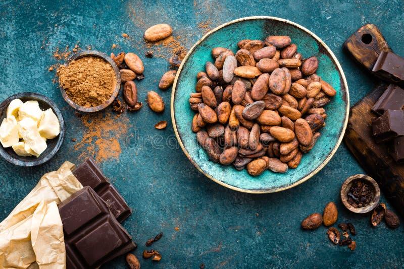 какао Бобы кака, темные ломти горького шоколада, масло какао и бурый порох стоковое изображение