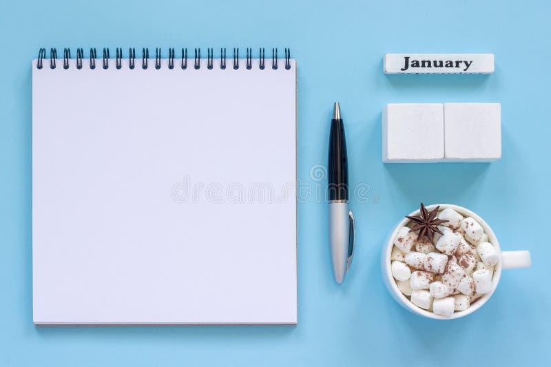 Какао чашки в январе календаря и зефир, пустой открытый блокнот стоковые изображения