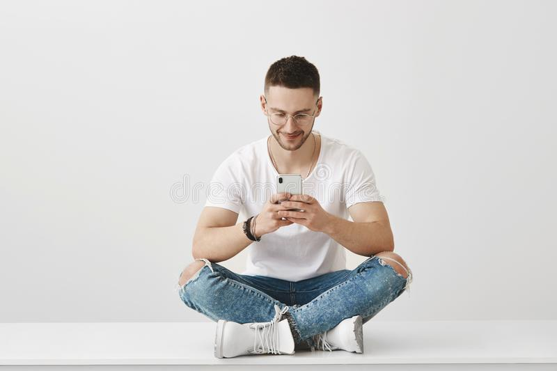 Какой внушительный app я загрузил Студия сняла привлекательного молодого сотрудника сидя в ультрамодном обмундировании на поле с стоковые фото