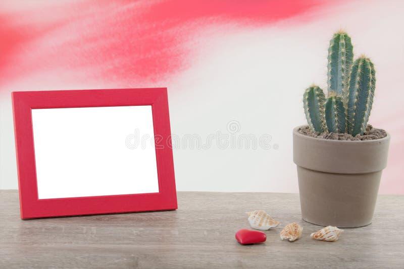 Кактус с рамкой фото на деревянном столе стоковая фотография