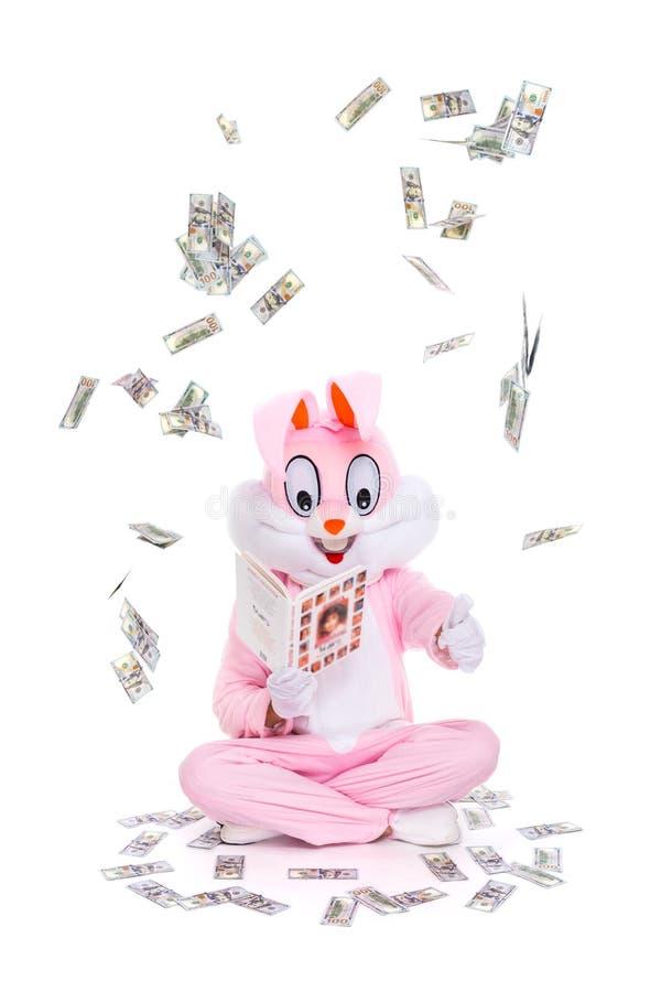 Как быть миллионером или миллиардером Знание сила Богатый удачливый человек читает книгу, сидит под дождем долларов стоковое изображение