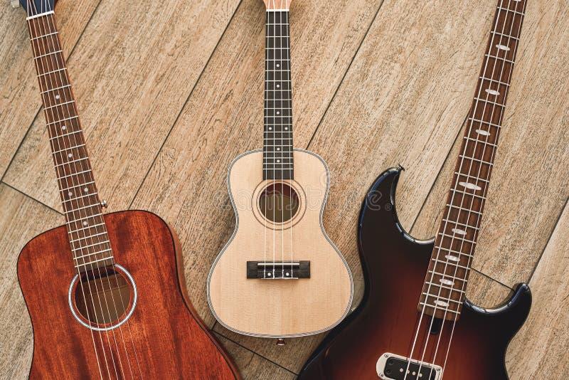 Как выбрать ваш первый взгляд сверху гитары на 3 разных видах гитар: акустический, электрический и гавайская гитара стоковая фотография rf