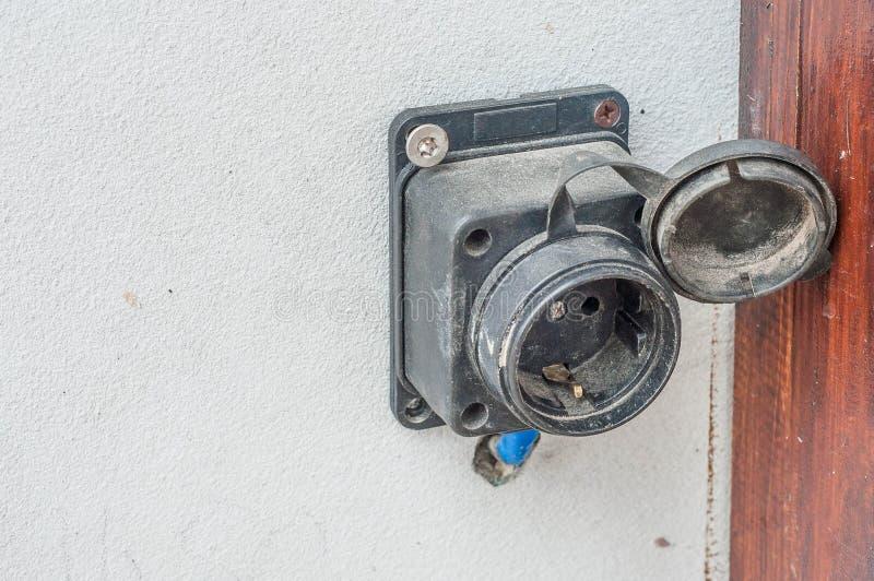 Как извлечь электрический выход на фасаде дома и исправить его на стен стоковое изображение rf