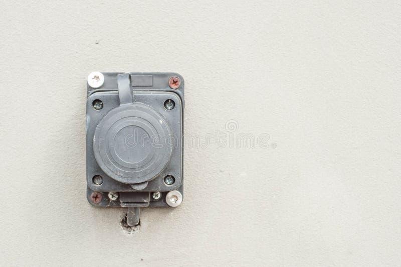 Как извлечь электрический выход на фасаде дома и исправить его на стен стоковые изображения rf
