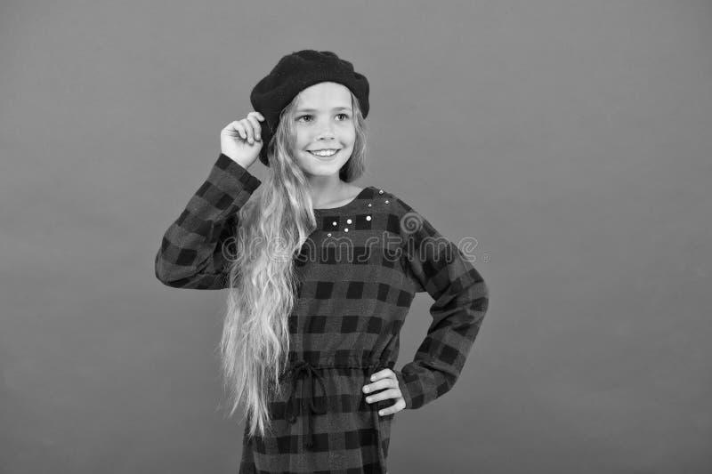 Как нести берет как девушка моды Девушка ребенк маленькая милая с длинными волосами представляя в предпосылке шляпы красной Модны стоковое фото rf